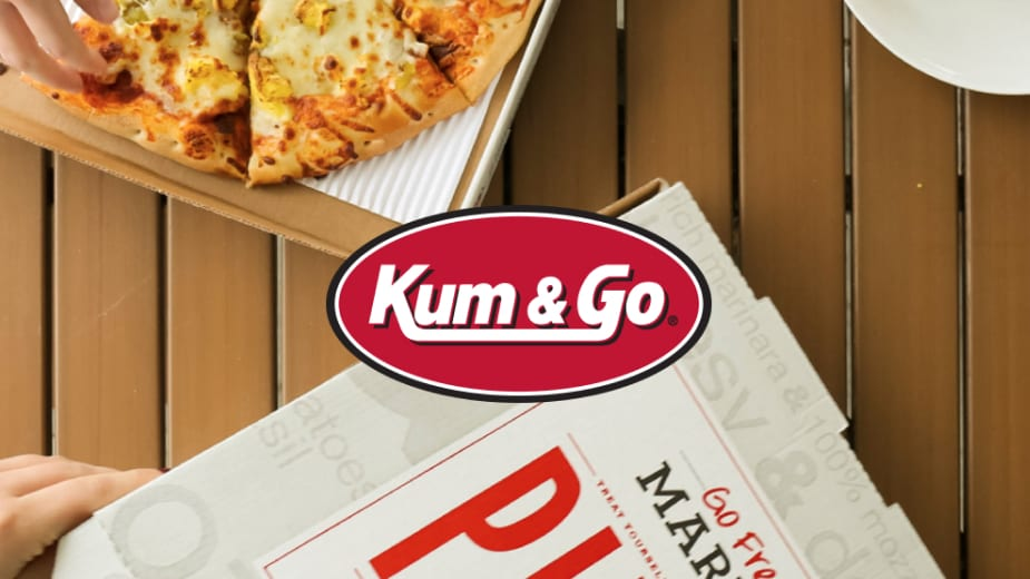 Pizza on a picnic table with the Kum & Go logo over it